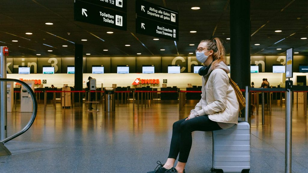 A woman wearing a mask sitting on her luggage at the airport during Covid-19 pandemic