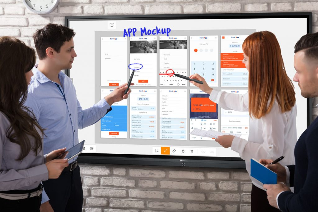A man and a woman are using styluses to draw on Meetboard interactive display