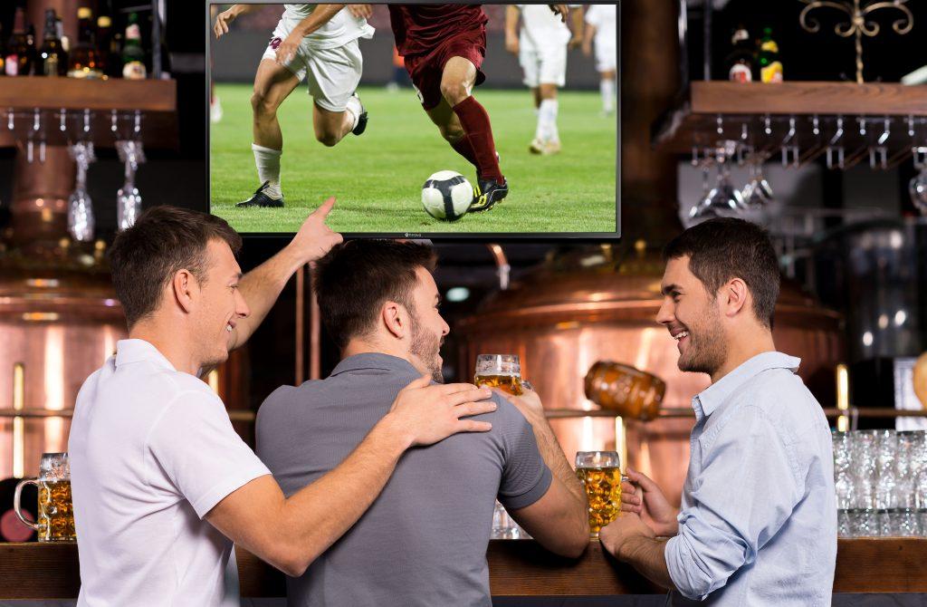 3 men are drinking in front of digital menu board in a bar