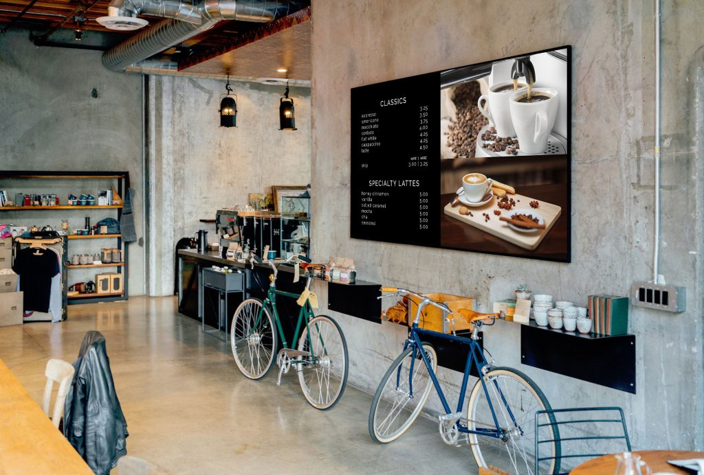 A digital menu board is installed in a cafe