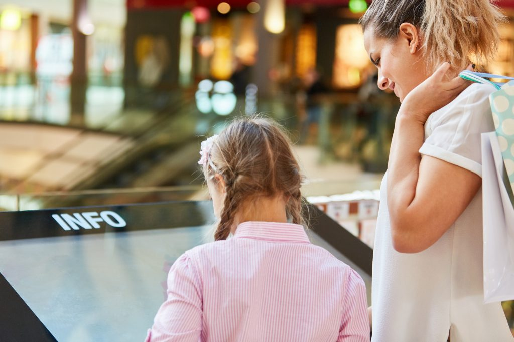 A mom with her daughter is using an interactive digital signage in a shopping mall