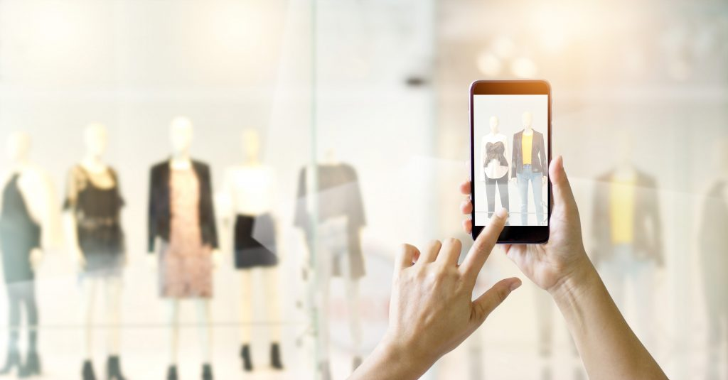 A person is using a mobile phone to find information related to the clothes