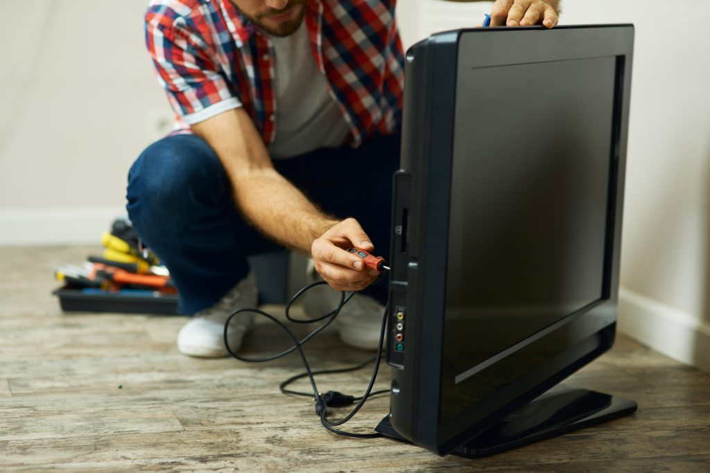 A man is fixing a consumer TV in a room